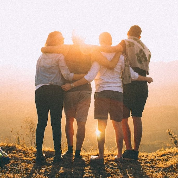 Friends embracing and facing sunrise
